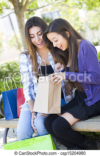 Young Adult Mixed Race Women Looking Into Their Shopping Bags - csp15204980