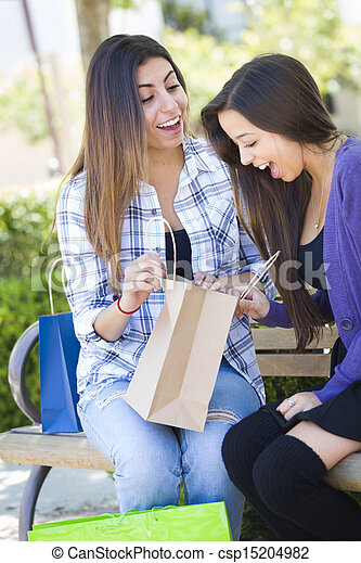 Young Adult Mixed Race Women Looking Into Their Shopping Bags - csp15204982