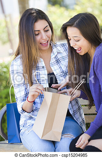 Young Adult Mixed Race Women Looking Into Their Shopping Bags - csp15204985