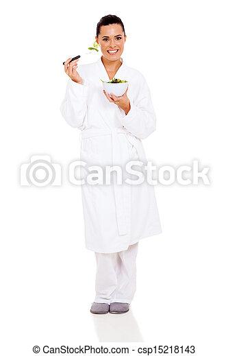 beautiful woman in pajamas eating green salad - csp15218143