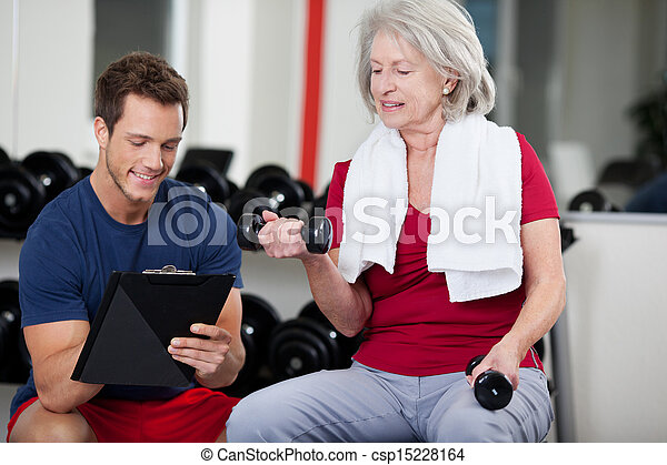 Trainer instructing a senior woman in the gym - csp15228164