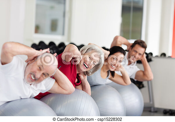 Smiling elderly woman training in a group - csp15228302