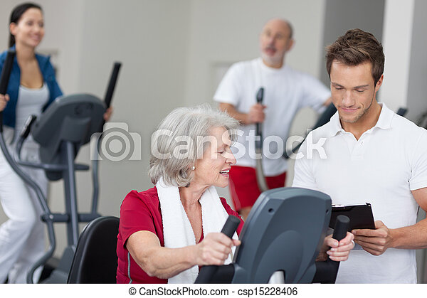 Senior woman with a personal fitness trainer - csp15228406