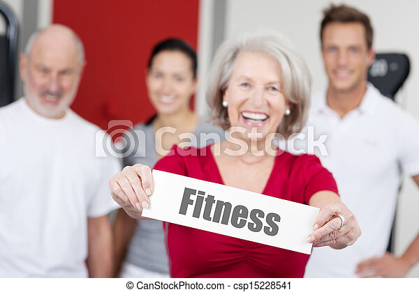 Senior Woman Holding Fitness Sign With Family In Background - csp15228541