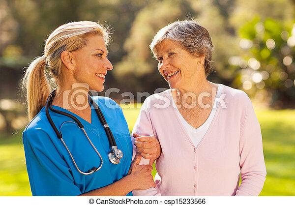 nurse talking to senior woman outdoors - csp15233566