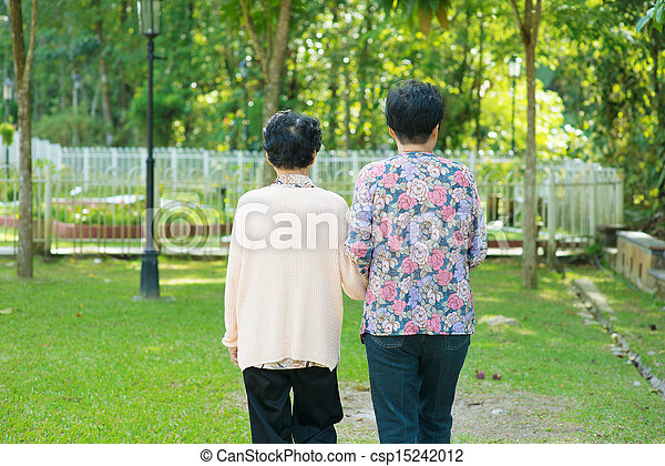 Rear view of Asian 80s old mother and 60s senior daughter holding hands walking at outdoor park. - csp15242012