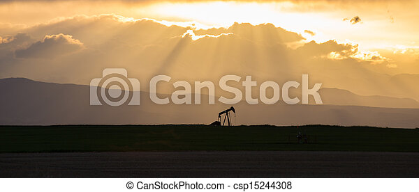 Pumpjack with Crepuscular Rays and Rocky Mountains - csp15244308