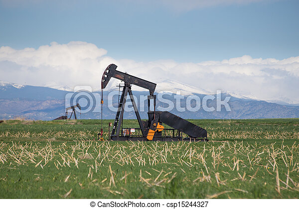 Pump Jacks in Green Field With Snow Covered Rocky Mountains and Blue Sky - csp15244327