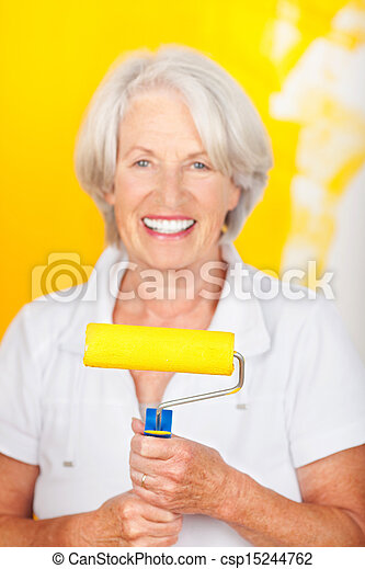 Smiling senior woman painting her home