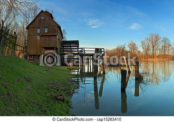 Historic wooden watermill with reflection. - csp15263410