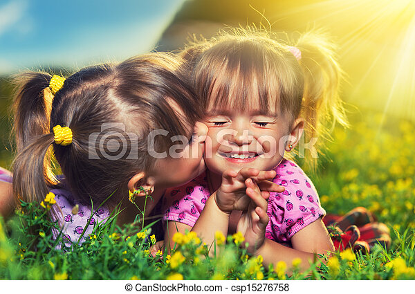happy family. little girls twin sisters kissing and laughing in the summer outdoors - csp15276758