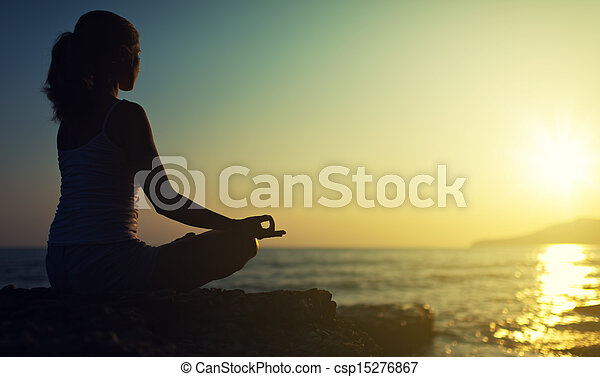 yoga outdoors. silhouette of a woman sitting in a lotus position on the beach at sunset - csp15276867