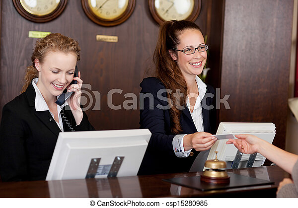 Two receptionists at a reception desk - csp15280985