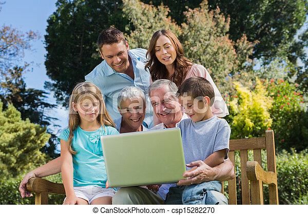 Smiling multi generation family with a laptop sitting in park - csp15282270