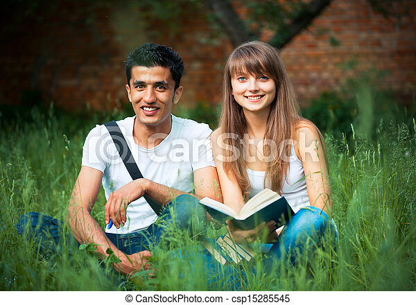 Two students guy and girl studying in park on grass with book - csp15285545
