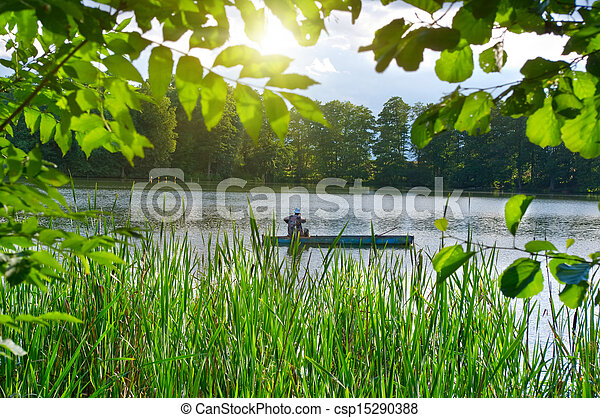 Inveterate fisherman in a boat on the lake. Summer fishing - csp15290388