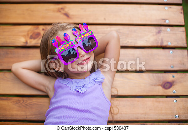 Adorable little girl in Happy Birthday glasses have fun outdoor - csp15304371