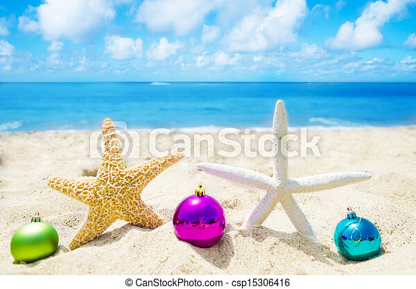 Two Starfishes with Christmas balls on sandy beach in sunny day- holiday concept - csp15306416