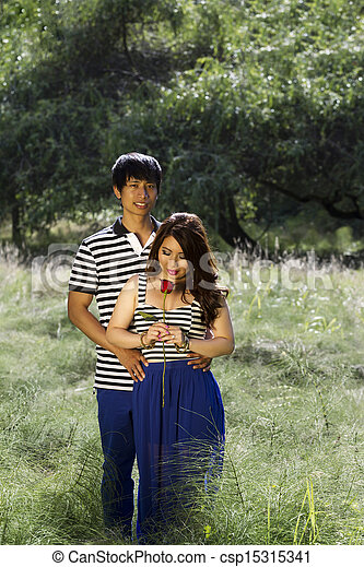 Vertical photo of young adult couple with woman looking at single red rose in the middle of a bright green grass field - csp15315341