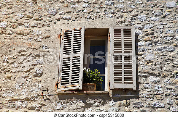 french rustic window with old wood shutters in stone rural house, Provence, France. - csp15315880