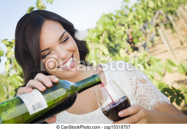 Young Adult Woman Enjoying A Glass of Wine in Vineyard - csp15319757