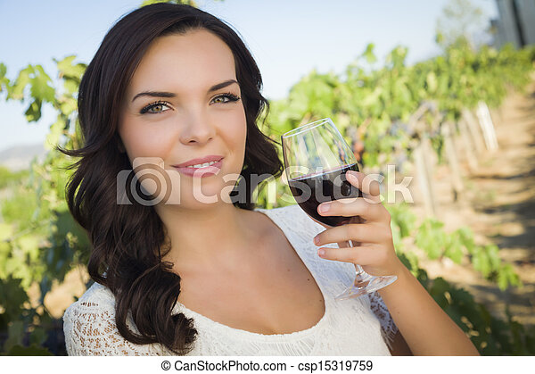 Young Adult Woman Enjoying A Glass of Wine in Vineyard - csp15319759