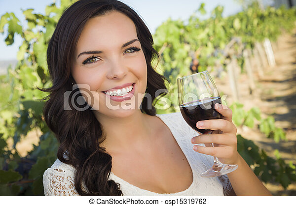 Young Adult Woman Enjoying A Glass of Wine in Vineyard - csp15319762