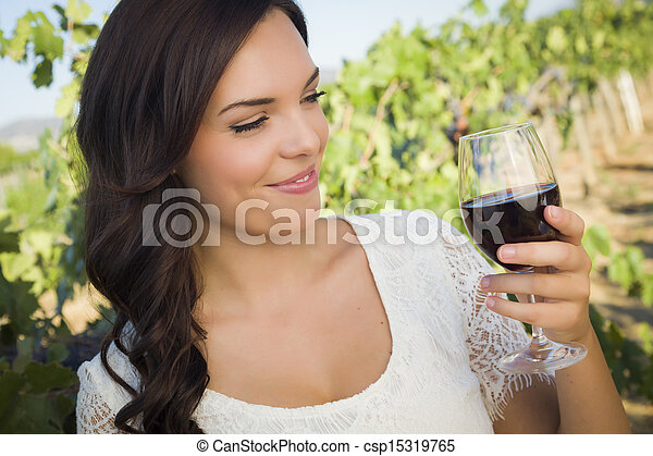 Young Adult Woman Enjoying A Glass of Wine in Vineyard - csp15319765