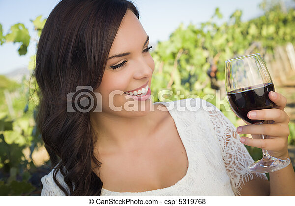 Young Adult Woman Enjoying A Glass of Wine in Vineyard - csp15319768