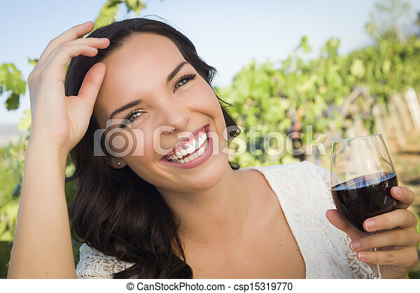 Young Adult Woman Enjoying A Glass of Wine in Vineyard - csp15319770