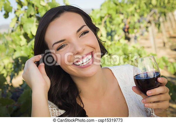Young Adult Woman Enjoying A Glass of Wine in Vineyard - csp15319773