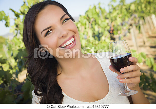 Young Adult Woman Enjoying A Glass of Wine in Vineyard - csp15319777