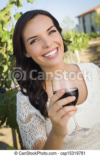 Young Adult Woman Enjoying A Glass of Wine in Vineyard - csp15319781