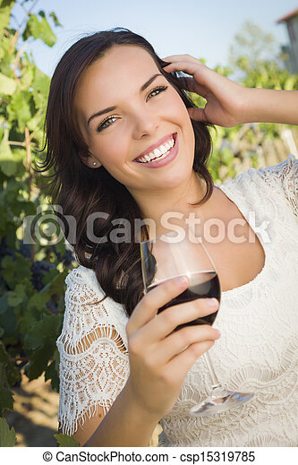 Young Adult Woman Enjoying A Glass of Wine in Vineyard - csp15319785