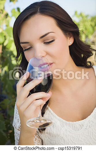 Young Adult Woman Enjoying A Glass of Wine in Vineyard - csp15319791