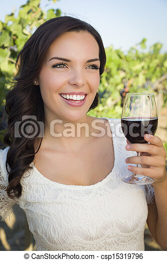 Young Adult Woman Enjoying A Glass of Wine in Vineyard - csp15319796