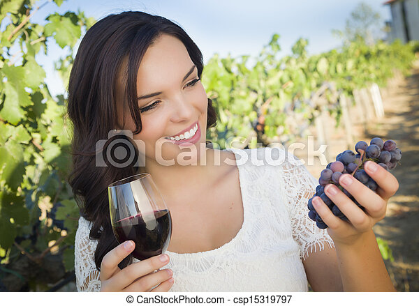 Young Adult Woman Enjoying A Glass of Wine in Vineyard - csp15319797