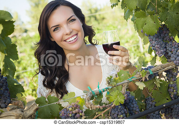 Young Adult Woman Enjoying A Glass of Wine in Vineyard - csp15319807