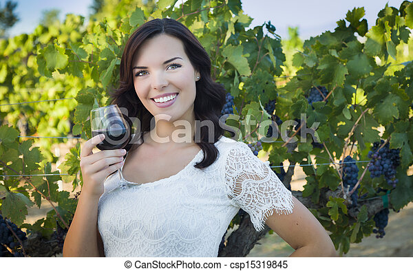Young Adult Woman Enjoying A Glass of Wine in Vineyard - csp15319845