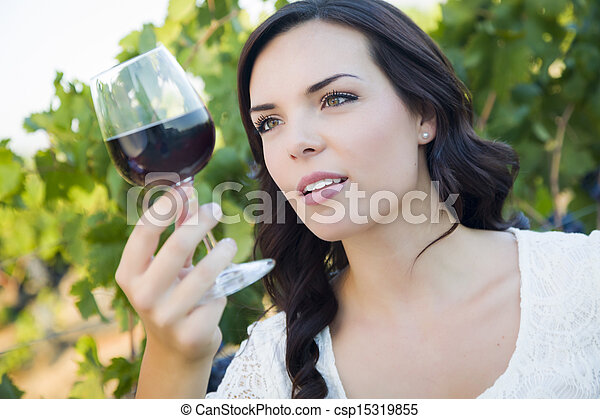 Young Adult Woman Enjoying A Glass of Wine in Vineyard - csp15319855