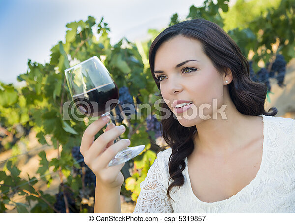 Young Adult Woman Enjoying A Glass of Wine in Vineyard - csp15319857