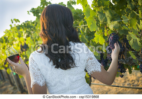 Young Adult Woman Enjoying A Glass of Wine in Vineyard - csp15319868