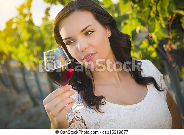Young Adult Woman Enjoying A Glass of Wine in Vineyard - csp15319877