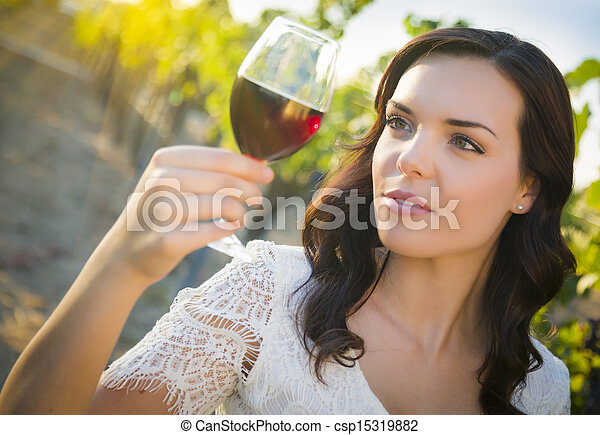 Young Adult Woman Enjoying A Glass of Wine in Vineyard - csp15319882