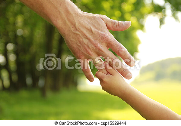 hand of parent and child in nature - csp15329444