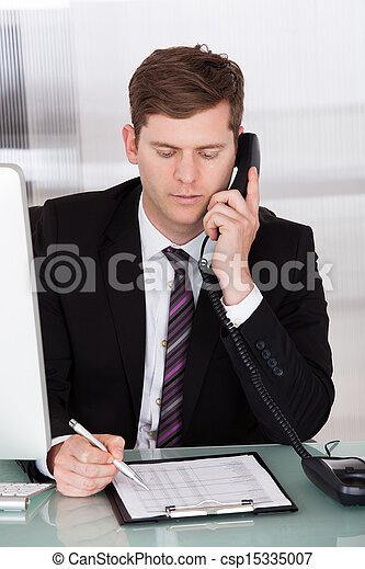 Businessman talking on telephone in office - csp15335007