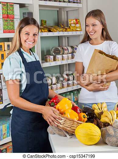 Saleswoman Holding Vegetable Basket With Female Customer - csp15347199