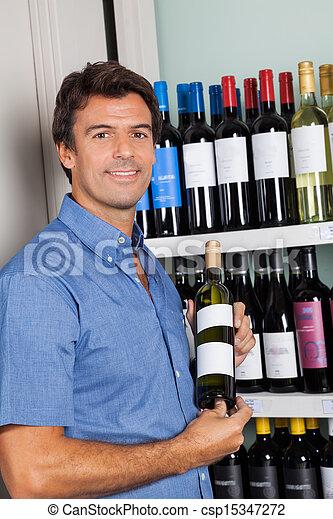 Portrait Of Man Showing Alcohol Bottle - csp15347272