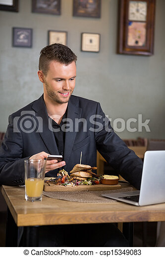 Businessman Using Laptop While Having Food In Restaurant - csp15349083