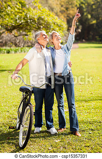 middle aged couple walking in park - csp15357331